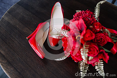 A pair of red high-heeled shoes with a bouquet on the table