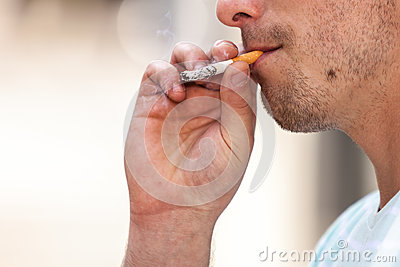 Adult man smoking cigarette outside