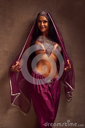 Belly-dancer woman in afghani pants, purdah and adornment