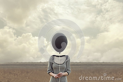 Woman`s head replaced by a black balloon