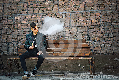 Vape. A young handsome guy sits on the bench and blows steam from an electronic cigarette.