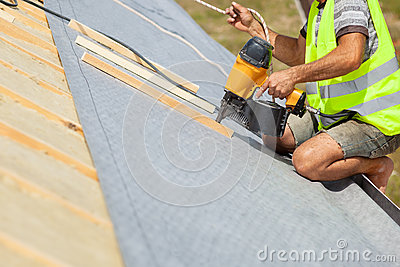 Roofer builder worker use automatic nailgun to attach roofing membrane.
