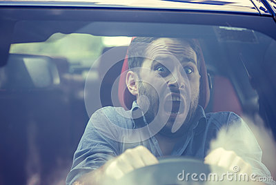Man driving a car shocked about to have traffic accident, windshield view