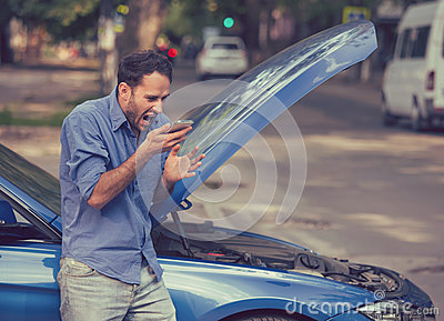 Frustrated young man calling roadside assistance after breaking down