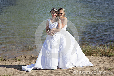 Just married happy lesbian couple in white dress embrace near sm