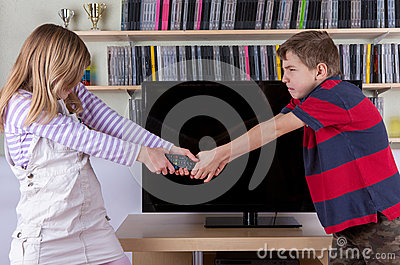 Siblings fighting desperatelly for the TV remote control in front of the televison