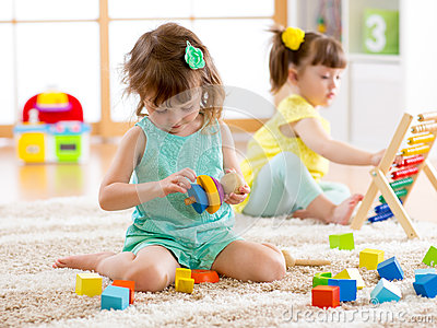 Children toddler and preschooler girls play logical toy learning shapes, arithmetic and colors at home or nursery