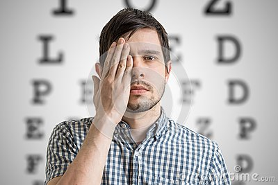 Young man is covering his face with hand and checking his vision. Chart for eye sight testing in background