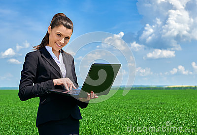 Business woman in green grass field outdoor work on laptop. Young girl dressed in black suit. Beautiful spring landscape with clou