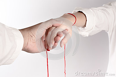 A hand of couple touch each other. The Faith of red thread brings destiny