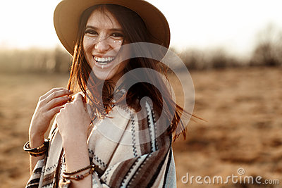stock image of beautiful boho woman hipster, smiling, wearing hat and poncho at sunset in mountains, true emotions, space for text