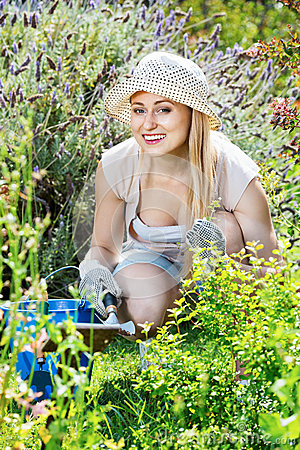 Woman working in garden using horticultural instruments on summer day
