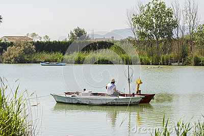 Fisherman on a boat. Fresh water lagoon in Estany de cullera. Valencia, Spain