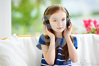 Cute girl wearing huge wireless headphones. Pretty child listening to the music. Schoolgirl having fun listening to kid`s songs at