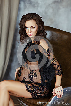 Beautiful, glamorous and pregnant woman in black fishnet dr