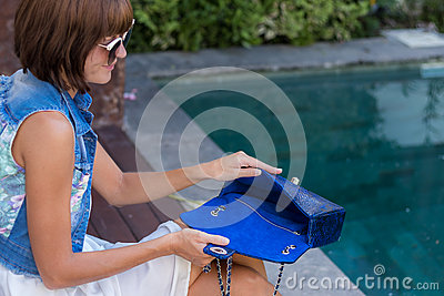 Young stylish woman in trendy outfit with snakeskin python luxury bag in hands. Woman with handbag near the swimming