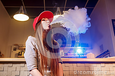 Young pretty woman in red cap smoke an electronic cigarette at the vape shop