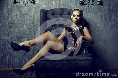 Portrait of young gorgeous long legged model with ponytail and artistic make-up wearing short sequin golden dress