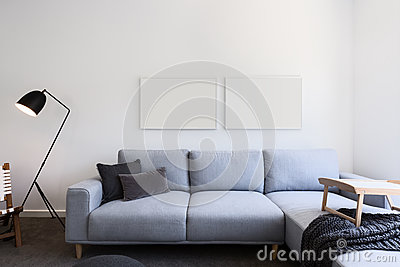 Pale blue linen sofa and blank pictures in a living room