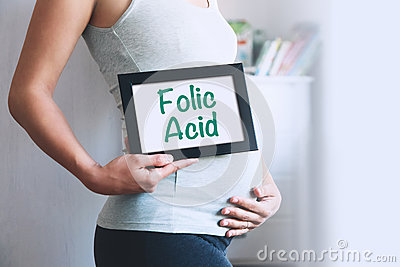 Pregnant woman holds whiteboard with text message - FOLIC ACID