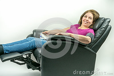 Middle-age woman leaning back in black leather recliner armchair. Checking blood pressure using portable blood pressure machine.