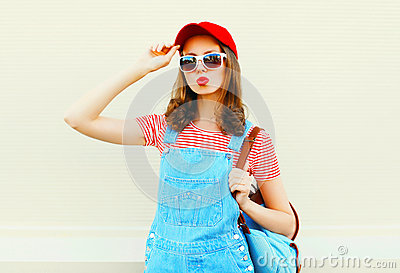 Fashion young pretty woman wearing a denim jumpsuit with baseball cap and sunglasses over white