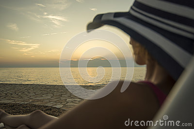 Woman with sunhat overlooking the ocean