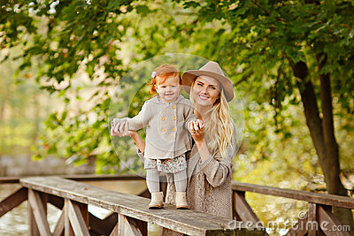 Mum gently embraces the redhead baby girl and laughing in autumn