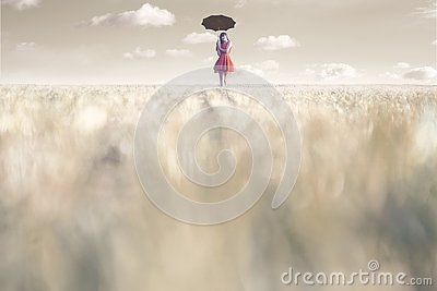 Woman shelters from the sun with her umbrella in a surreal place