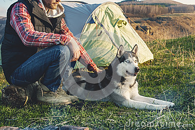 Close-up Guy bearded in jeans checkered shirt and a sleeveless jacket with a dog husk on vacation sitting on nature next