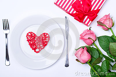 Romantic dinner: plate, cutlery and roses on a white background.