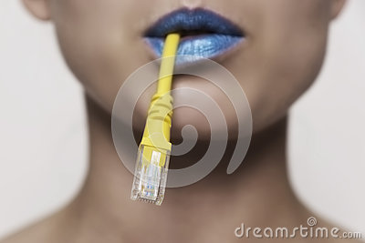 Close-up of a female face holding a network cable in her mouth