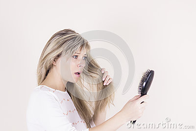 Hair loss. Depressed young woman looking at her hairbrush and expressing negativity