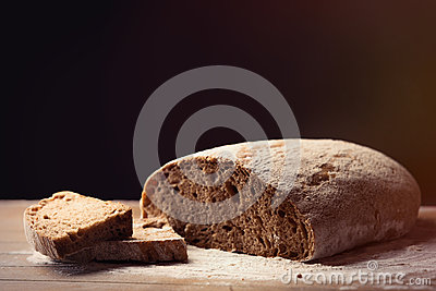 Photo of tasty fresh loaf of bread on the wonderful brown wooden