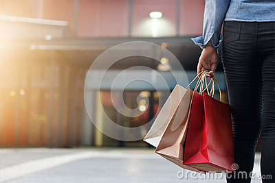 Woman walking with shopping bags on shopping mall background