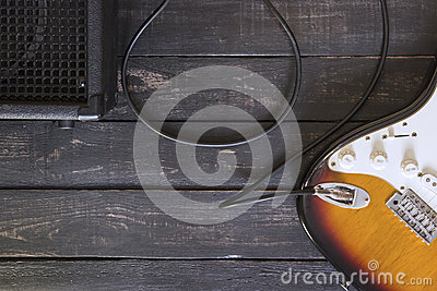 Electric guitar and black amplifier connected by cable on wooden