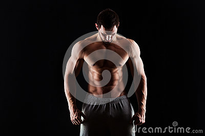 Muscular and torso of young man having perfect abs, bicep and chest. Male hunk with athletic body. Fitness concept