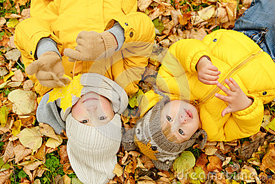 Two brothers in yellow jackets autumn leaves lie on