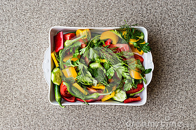 Salad with dill, yellow pepper, red pepper, parsley, tomato and cucumber in white bowl.
