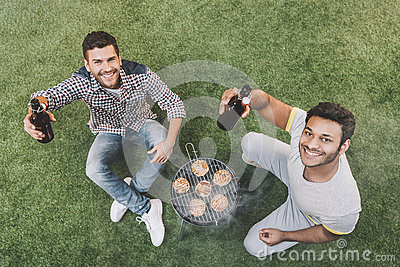 Happy young men sitting on grass with beer bottles and making barbecue