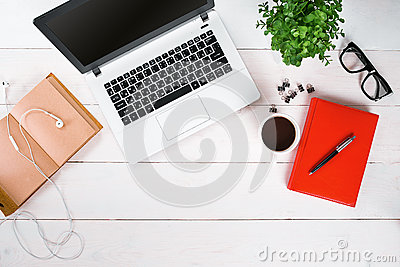 Laptop, digital tablet, diary, coffee cup and potted plant on work desk.