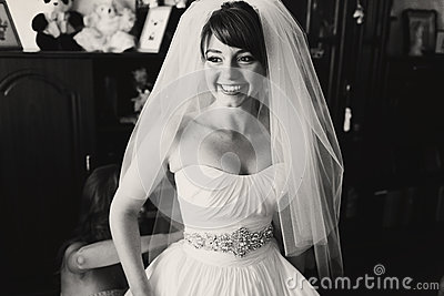 Bride smiles sincerely while bridesmaid buttons up her dress