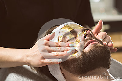 Men`s gold mask therapy at beautician`s