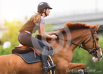 Young pretty girl riding a horse with backlit leaves behind in s