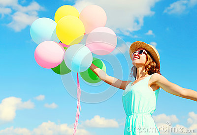 Happy young smiling woman holds an air colorful balloons is having fun wearing a summer straw hat over a blue sky background