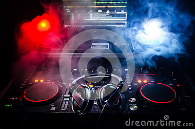 DJ Spinning, Mixing, and Scratching in a Night Club, Hands of dj tweak various track controls on dj's deck, strobe lights and fog,