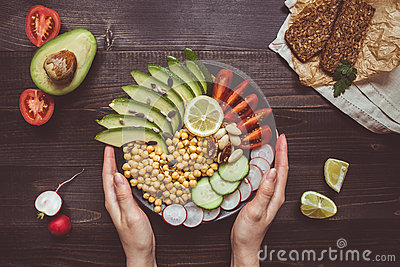Healthy food concept. Hands holding healthy salad with chickpea and vegetables. Vegan food. Vegetarian diet
