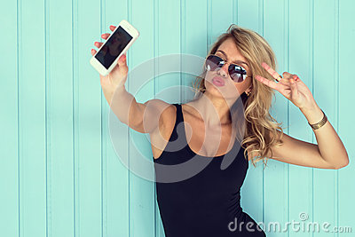 Blonde woman in bodysuit with perfect body taking selfie smartphone toned instagram filter