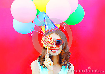 Portrait happy smiling woman in a birthday cap closes her eye with a lollipop on stick over an air colorful balloons on pink bac