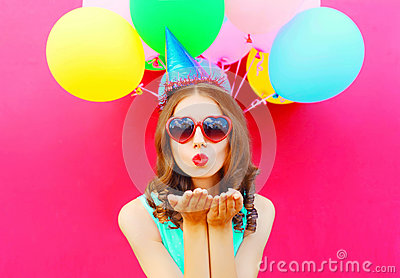 Portrait pretty woman in a birthday cap is sends an air kiss holds an air colorful balloons on pink background